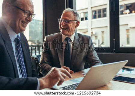Two caucasian partners having business meeting at the cafe. Senior businessmen sitting at coffee shop table with laptop and laughing.