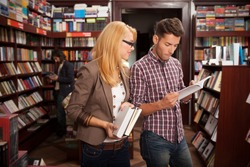 two caucasian young people in a bookstore reading something in a book with many bookshelves in the background