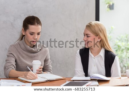 Two Caucasian young woman discuss job in the office - Shutterstock ID 683255713