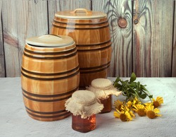 Two ceramic barrels and two glass jars with honey and yellow flowers on a wooden background. Horizontal orientation