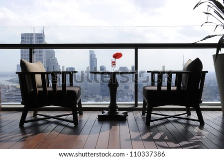 two chair at terrace restaurant with city view background