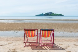 Two chairs are set up on the beach by the sea, good atmosphere, bright sunshine.