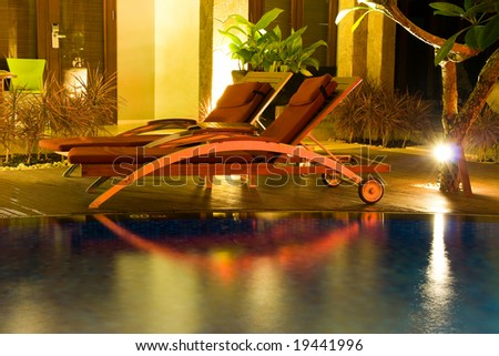 Two chairs by the swimming pool in the night