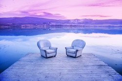 Two chairs on the shore of lake during sunset - contemplation, thinking, communcation, dialog - concept photo