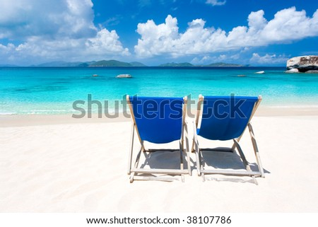 two chairs on tropical beach with turquoise waters