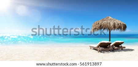 Two Chairs Under Parasol In Tropical Beach