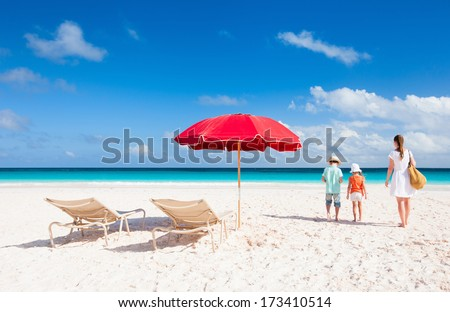 Two chairs under umbrella on a beautiful tropical beach with family walking nearby #173410514