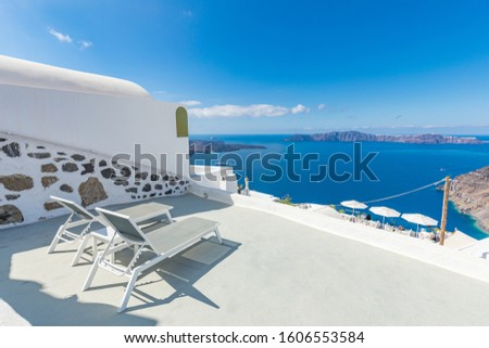 Two chaise lounges on the terrace with sea view. Santorini island, Greece. Luxury summer vacation destination, honeymoon destination, romantic view