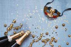 Two champagne bottles with carnival mask, confetti stars and party streamers on blue background. Flat lay of Christmas, anniversary, carnival, New Year celebration concept. Copy space, top view.