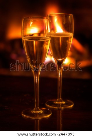 Two champagne flutes lit by log fire.  Soft focus effect.