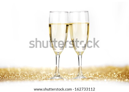 Two champagne flutes on gold shiny background