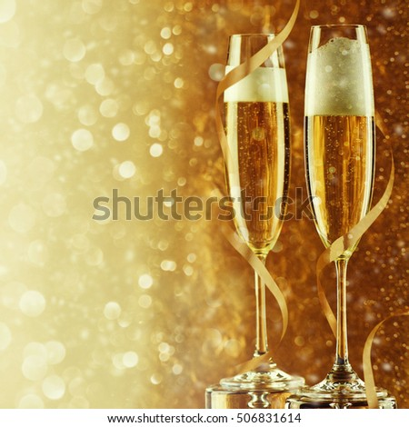Two champagne flutes on gold shiny background #506831614
