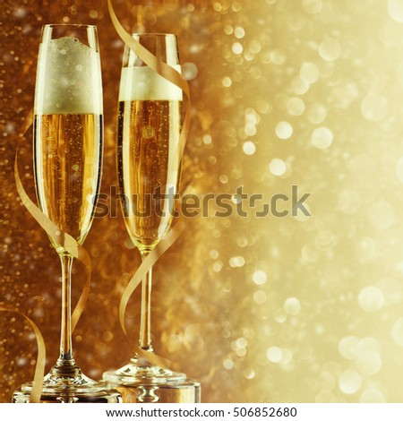 Two champagne flutes on gold shiny background #506852680