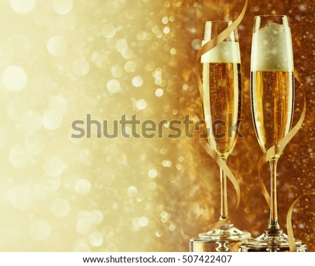 Two champagne flutes on gold shiny background #507422407