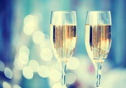 Two champagne glass on christmas bokeh background. Blue toned
