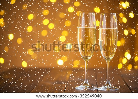 Two champagne glass on christmas bokeh background with snow #352549040