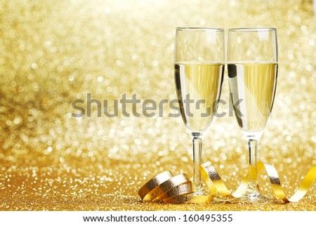 Two champagne glasses and decoration on golden background #160495355