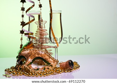 Two champagne glasses and venetian mask