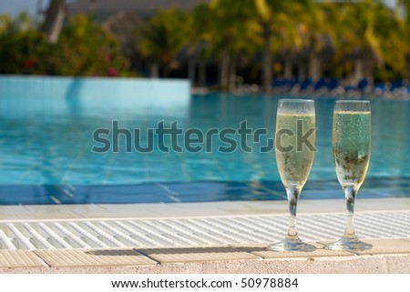 Two Champagne Glasses By The Side Of A Caribbean Resort Swimming Pool Ready For A celebration