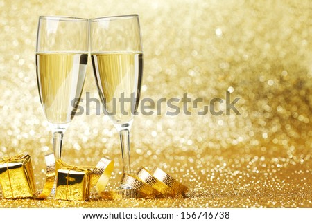 Two champagne glasses, gifts and decoration on golden background #156746738