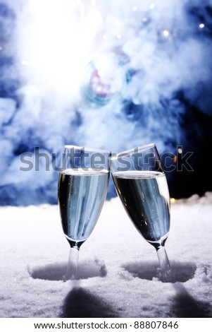 two champagne glasses in snow clink glasses for new year on sylvester firework in background