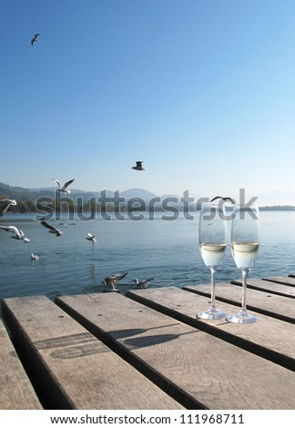 Two champagne glasses on a wooden jetty
