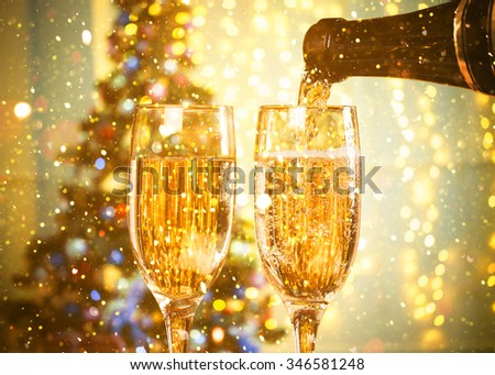 Two Champagne Glasses On Defocused Background Living Room With Christmas Tree and glitter lights #346581248