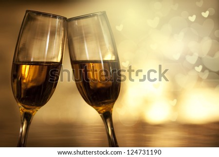 Two champagne glasses on golden background with heart shaped bokeh #124731190