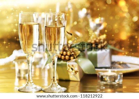 Two champagne glasses on the dinner table with gift boxes #118212922