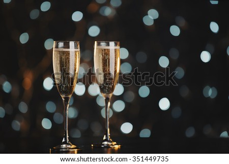 Two champagne glasses over dark bokeh background   #351449735