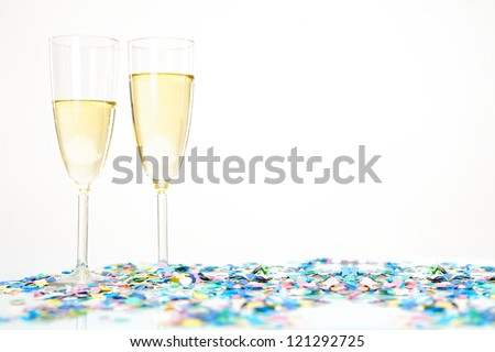 Two champagne glasses with alcohol and colored confetti decoration isolated on white background. Possible copy space