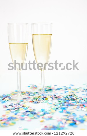 Two champagne glasses with alcohol and colored confetti decoration isolated on white background