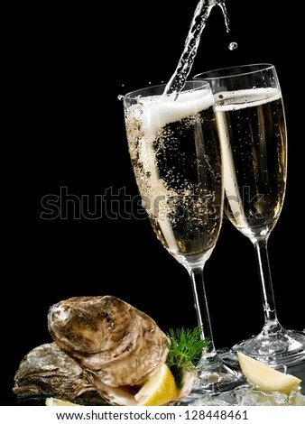Two champagne glasses with oysters and champagne pouring