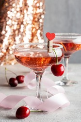 Two champagne glasses with pink champagne on party with berries and shine background