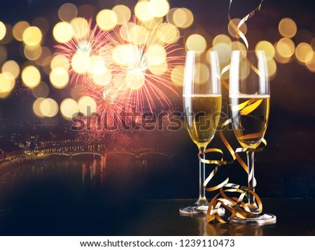 two champagne glasses with ribbons against holiday lights and fireworks - New Year celebrations #1239110473