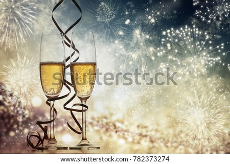 two champagne glasses with ribbons against holiday lights and fireworks - New Year celebrations #782373274
