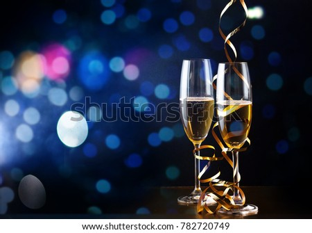 two champagne glasses with ribbons against holiday lights and fireworks - New Year celebrations #782720749