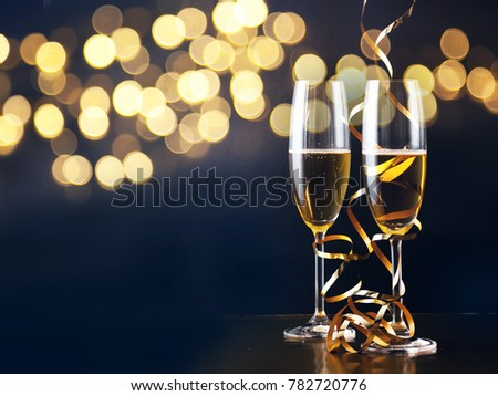 two champagne glasses with ribbons against holiday lights and fireworks - New Year celebrations #782720776