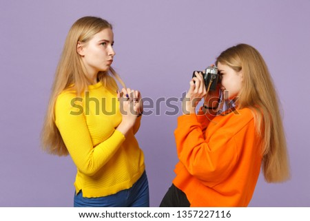 Two charming young blonde twins sisters girls in colorful clothes taking pictures on retro vintage photo camera isolated on violet blue background. People family lifestyle concept. Mock up copy space