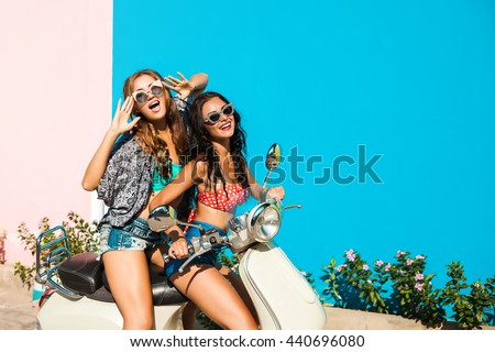 Two cheerful beautiful funny girl hipster, best friends, ride retro scooter, dressed in shorts, T-shirts, sexy bikini, sunglasses, laugh, screaming smile, crazy, fool around, gossiping, party, emotion