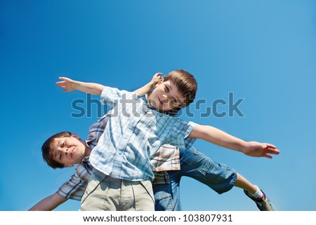 Two cheerful boys against blue sky