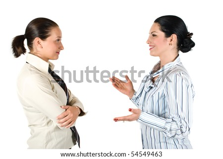 Two cheerful businesswoman have a conversation,the brunette woman explaining something and gesturing with hands while the other listen her very attentive