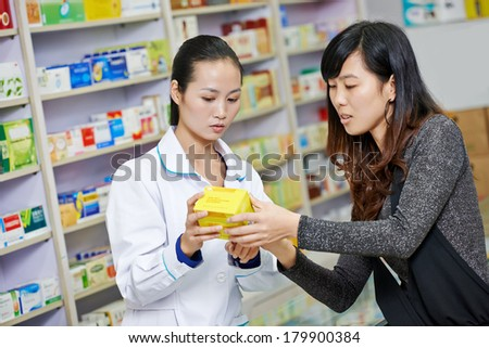 Two cheerful chinese pharmacist chemist woman standing in china pharmacy drugstore