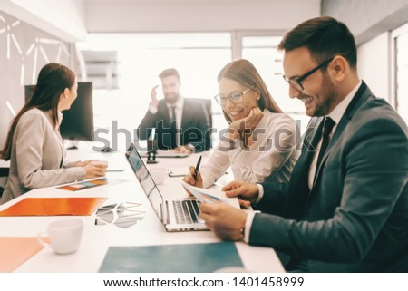 Two cheerful colleagues in formal wear solving problem and looking at paperwork. In background employees talking. It is literally true that succeed best and quickest by helping others to succeed.