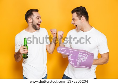 Two cheerful excited men friends wearing blank t-shirts standing isolated over yellow background, cheering with foam glove and beer #1378205234