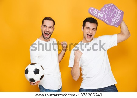 Two cheerful excited men friends wearing blank t-shirts standing isolated over yellow background, cheering with foam glove and football #1378205249