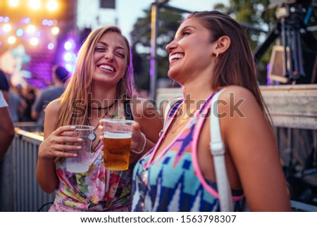 Two cheerful females having a good time at an outdoor festival
