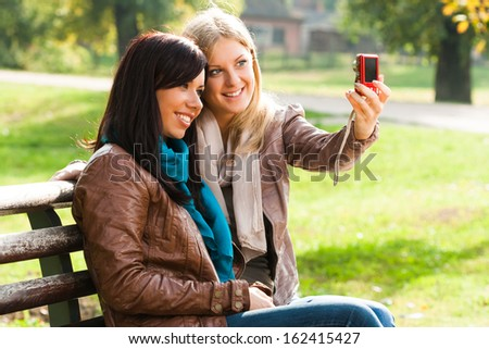 Two cheerful friends having fun and taking photos of themselves with camera,Girls taking a photo