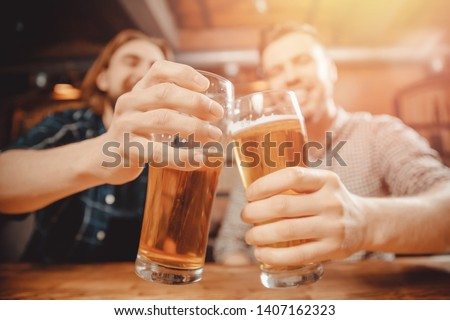 Two cheerful friends sit in sports bar and clink glasses with beer. Friendship concept, hockey fans. #1407162323