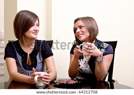 Two cheerful girls. Drinking tea and communicating.
